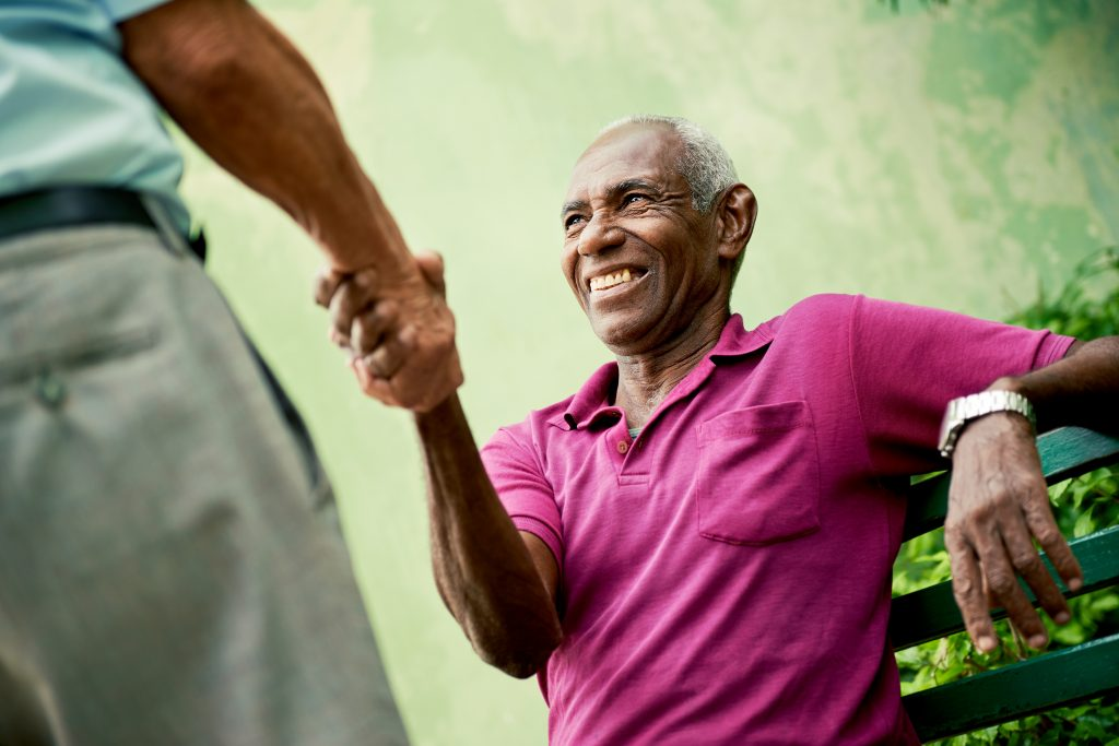 An image of two elderly men in the Caribbean shaking hands in a park.